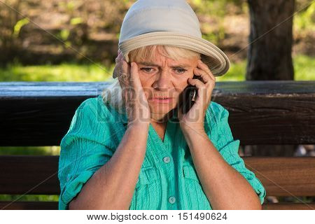 Stressed woman with phone. Senior lady in hat. This is terrible news. Don't know how to help.