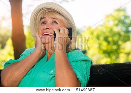 Cheerful woman with cell phone. Happy senior lady. Hello from far relatives. Nice to hear your voice.