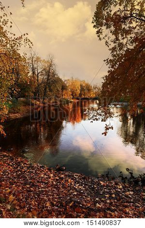 in city Park the evening sky and the colourful autumn trees reflected in the water of the big pond