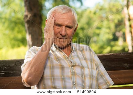 Old man holds his head. Elderly male has headache. Stress is bad for health. Years go by.