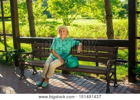 Mature woman is smiling. Lady sits on park bench. Best time is now. Strong health and positive attitude.