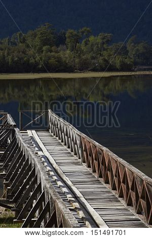 Wooden jetty on the edge of the calm waters of Lake Rosselot located along the Carretera Austral  in the Aysen Region of southern Chile.