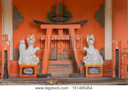 Kyoto Japan - September 15 2016: Orange colored altar with two white porcelain foxes and one Torii at Koanin Shinto shrine. Fox is considered the messenger between here and the afterlife.