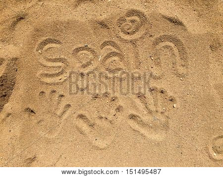 Three hand prints in the sand in Spain with the word Spain written in the sand.