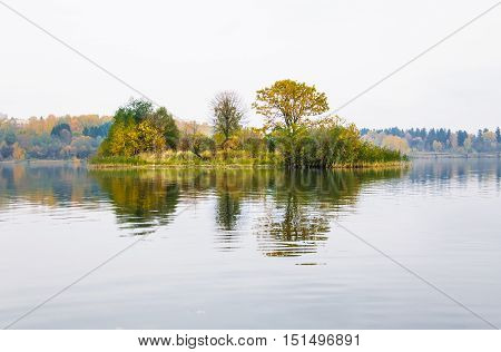 Raspberry island on lake Senezh in Solnechnogorsk fall in the fog in calm weather. Autumn water landscape