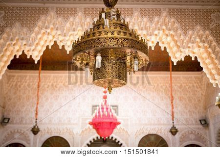 A Moroccan chandelier with a red chandelier in the background