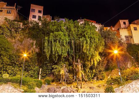 GUANAJUATO, MEXICO - DECEMBER 30, 2014 Famous Statue of Don Quixote and Sancho Panza night Plaza Allende Near Cervantes Theater Guanajuato Mexico. Guanajuato is in love with Cervantes the author and has a Cervantes Museum. This is one of the most popular