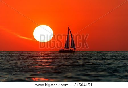 Sailboat sunset is a silhouetted boat with crew aboard sailing along the ocean water with a white hot sun setting in the red sunset sky.