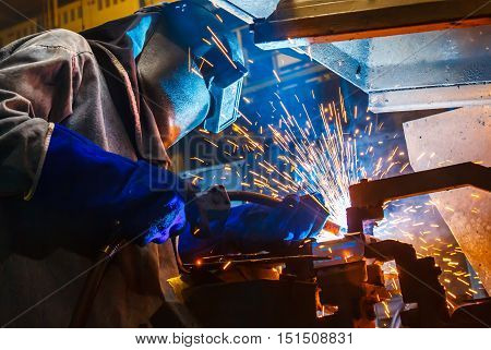 worker with protective mask welding metal. in Industrial automotive part. in car production factory.