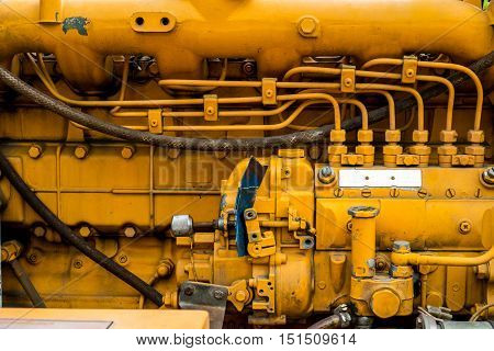 Old and dirty yellow diesel engine details.