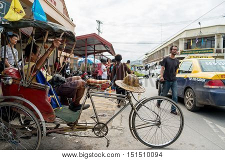 Phitsanulok Tailand- December 6 2015 : Trishaw driver resting on his vehicle among traffic at frontside of railway station by the way Phitsanulok railway station establish since january 24 1907. at Phitsanulok Thailand