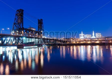 Water passes under the Steel Bridge in Portland with the convention center in the background