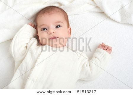 baby portrait lie on white towel in bed