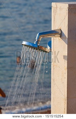 shower head with water droplets on seashore and blue sky background