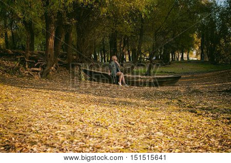 Pretty Blonde Sitting In A Wooden Old Boat Which Is On The Ground Laid By Yellow Fallen Autumn Leave