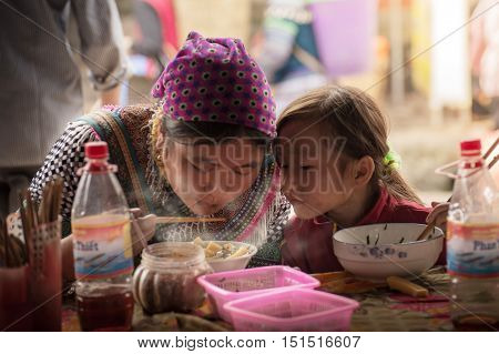 Sapa, Vietnam-September 2016: A mother has a meal with her child in Bancha market. The innocence of Munk kid in Sapa, Vietnam. Noodles or bancha is a common food in Vietnam.