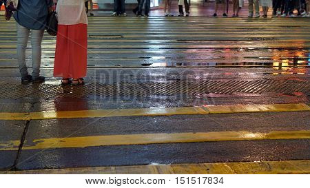 Asian People Cross Wet Street With Neon Light Reflection