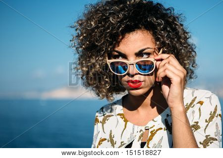 Portrait of mixed race beautiful girl with curly hair strictly looking over sunglasses