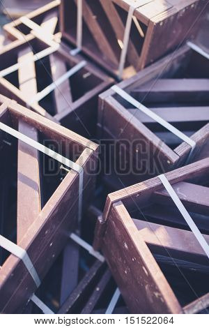 Wooden brown painted boxes or crates stacked in a pile at sunny autumn day. Outdoor scene.