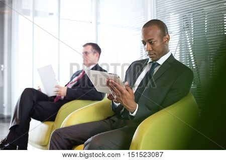 Young businessman using digital tablet on chair with male colleague in background at office