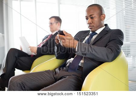 Young businessman using mobile phone on chair with male colleague in background at office