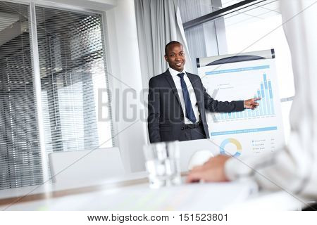 Confident young businessman pointing towards graph while giving presentation in office