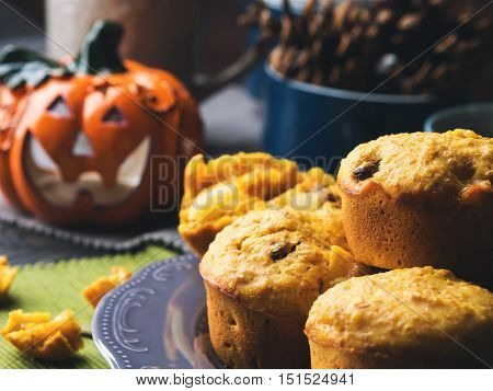 Pumpkin whole grain muffins with raisins and pumpkin seeds on dark background with a halloween decorative squash. Toned image