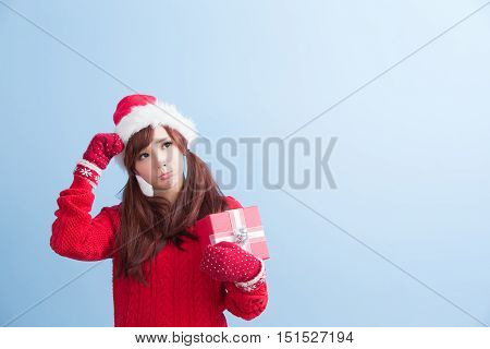 beauty woamn take gift and look smewhere in christmas isolated on blue background asian