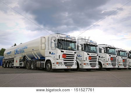 RAJAMAKI, FINLAND - JULY 2, 2016: Fleet of white Scania R480 semi tank trucks with ADR plates for Liquefied natural gas LNG transport parked on asphalt yard.