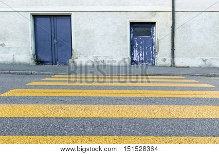 Yellow painted zebra crossing for pedestrians painted on an urban tarmac street looking towards the exterior wall and old grungy doors of a building low angle view