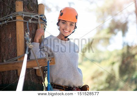 Deliriously happy. Optimistic cheerful young woman leaning on the tree and holding the rope while looking at you