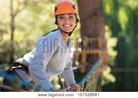 Joy and happiness. Joyful pretty slim woman leaning forwards and smiling while looking at you