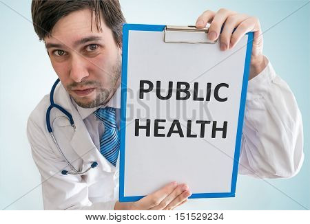 Doctor Is Showing Clipboard With Public Health Text Written. Vie