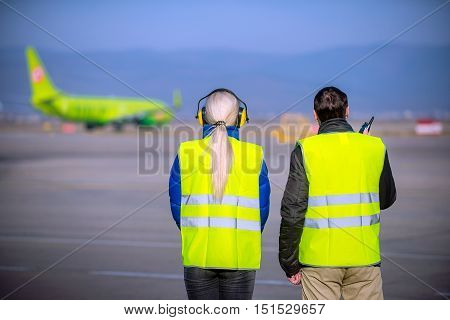 airport workers looking at an airplane as it departures