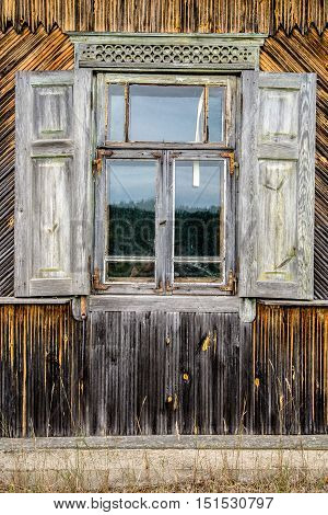 Closed glazed window of the old abandoned wooden house