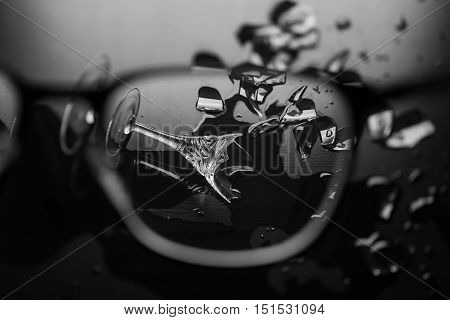 through glasses, an elegant wine glass is reflected in the spilled water, glass shards around on a dark background