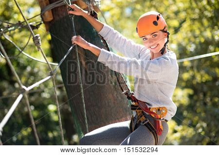 Being outdoors. Confident skillful elated woman holding on to the ropes and using special outfit while climbing on the ropes