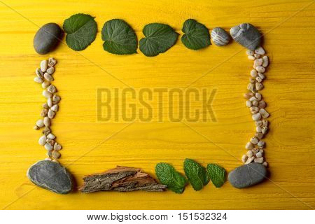 Rectangular frame made of  pebbles, leaves and bark on yellow wooden background