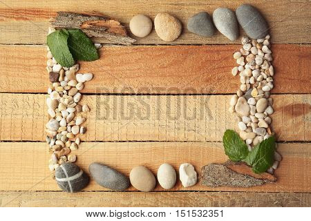 Rectangular frame made of pebbles, leaves and bark on wooden background