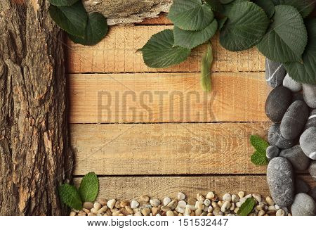 Rectangular frame made of leaves, pebbles and bark on wooden background