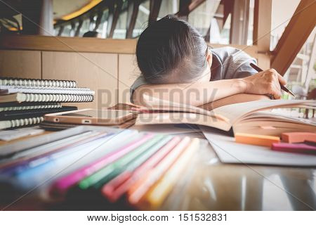 Female student sleeping at the desk with piles of book