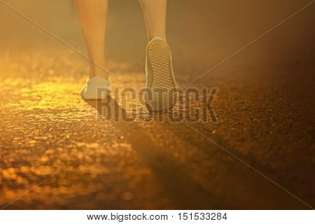 Female legs on asphalt background