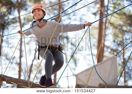 Taking pleasure in the moment. Charming joyful young woman standing on the rope ladder and smiling while enjoying herself