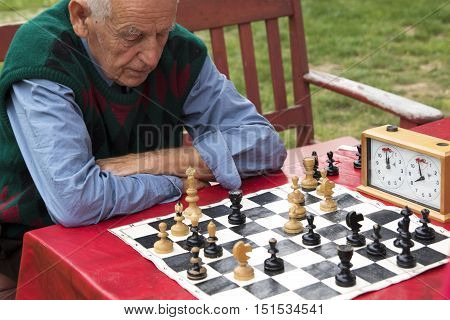 Mature man thinking and playing chess in the garden