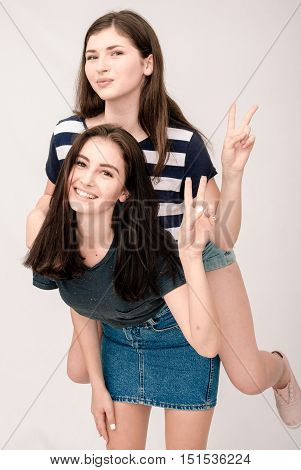 Positive friends portrait of two happy sister girls, funny faces, grimaces, joy, emotions, casual style on light grey background