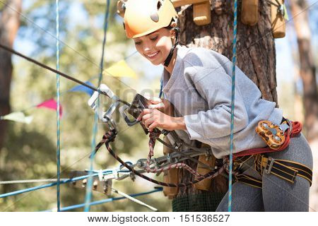 In a special outfit. Cute cheerful slim woman standing in front of the tree and leaning forward while fastening the mountain carabiner