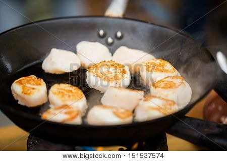 cooking, asian kitchen, sale and sea food concept - close up of scallops frying in cast iron pan at asian street market