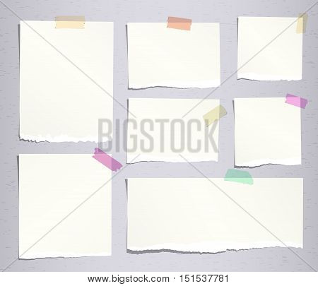 Pieces of beige ripped note, notebook paper sheets with colorful adhesive, sticky tape stuck on grey background.