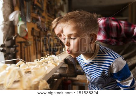 family, carpentry, woodwork and people concept - father and little son blowing shavings off wood plank at workshop