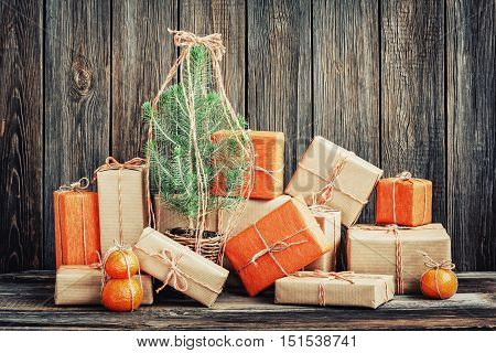 Vintage packages and young Christmas tree against the background of the old wooden boards